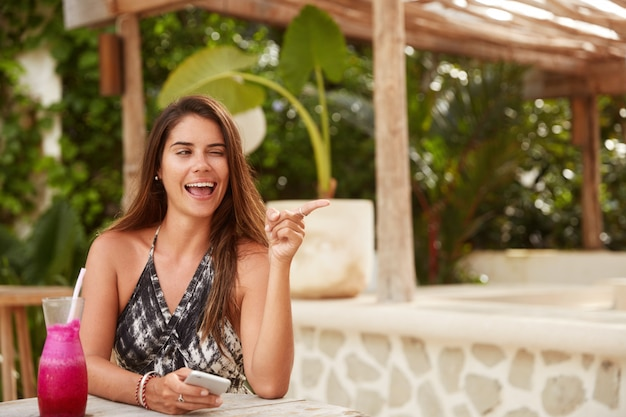 Funny beautiful woman has fun in sidewalk restaurant, blink eye and points at handsome guy, flirts, uses modern smart phone for surfing internet, enjoys fresh summer drink, being in exotic country