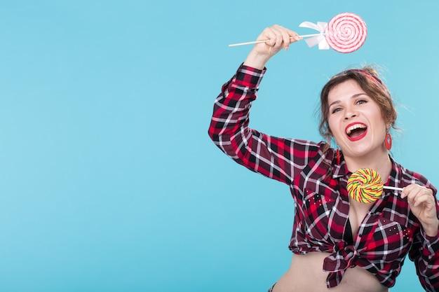 Copyspace와 파란색 표면에 포즈 다채로운 막대 사탕과 재미있는 아름 다운 젊은 핀-업 여자