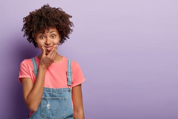 Bella giovane donna divertente con un afro che posa in tuta