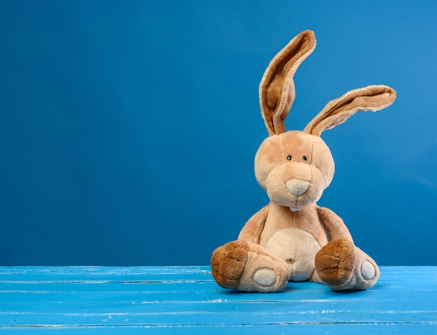 Funny beige plush rabbit with big ears and funny face on a blue background, copy space