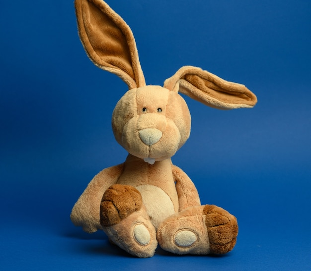 Funny beige plush rabbit with big ears and funny face on a blue wall