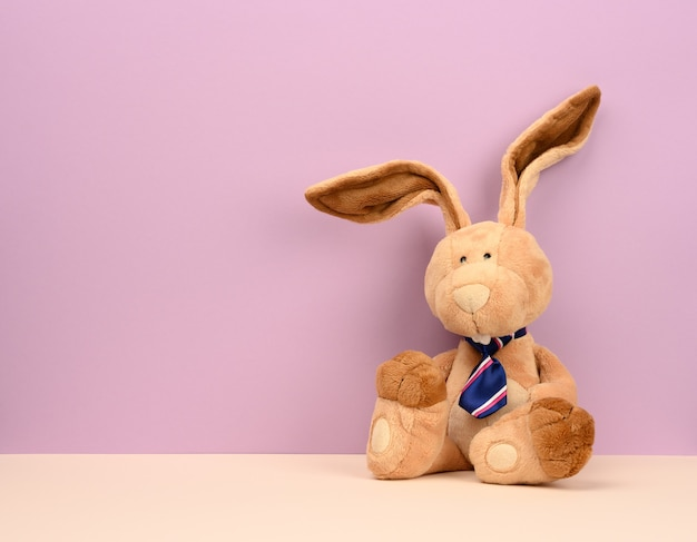 Funny beige plush rabbit with big ears and funny face, copy space