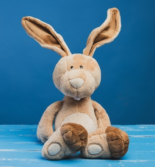 Funny beige plush rabbit with big ears and funny face