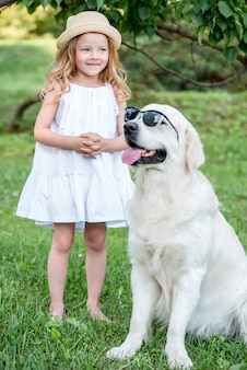 Funny big dog in sunglasses and cute blonde girl in white dress outdoors in park.