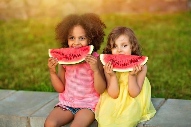 Смешные черные и европейские девушки едят арбуз на улице жарким летом