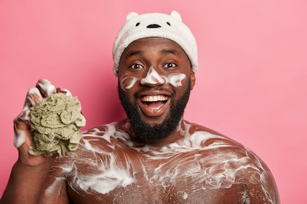 Funny black bearded man washes his torso, has foam on body and face, laughs happily, holds sponge, wears bath hat, isolated on pink background.