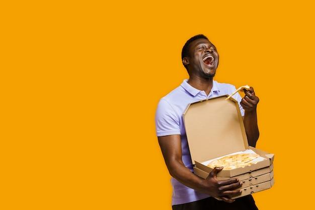 재미있는 흑인 택배가 웃고 4개의 피자 상자가 있는 피자 조각을 들고 있습니다. 레스토랑에서 맛있는 음식 피자 배달. 안전 배송.