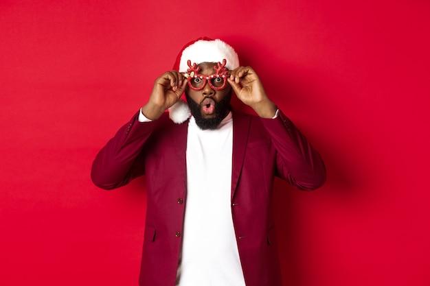 新年を祝う、パーティーグラスとサンタの帽子をかぶって、赤い背景の上で楽しんでいる面白い黒人男性