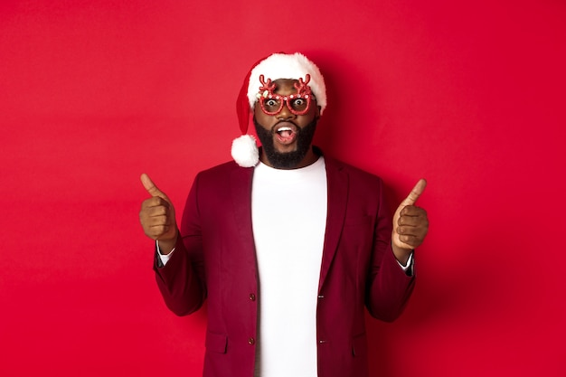 Funny black man celebrating new year, wearing party glasses and santa hat, showing thumb up, approve and like, standing over red background.