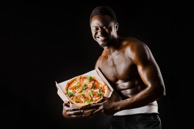 피자 미소와 함께 재미 있는 흑인입니다. 옷을 벗은 아프리카인은 안전한 음식 배달에서 일합니다. 레스토랑에서 음식으로 맞는 남자. 검은 벌거 벗은 남자.