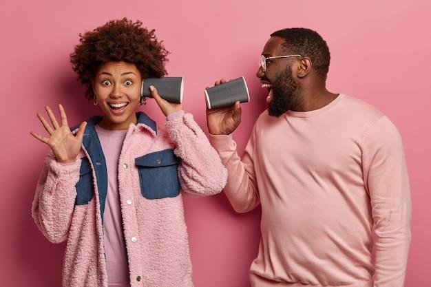 Uomo e donna di colore divertenti si sentono intrattenuti, scherzano, tengono bicchieri di carta vicino all'orecchio e alla bocca, indossano abiti color rosa pastello