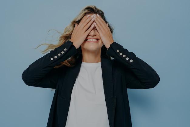 Смешная белокурая красивая женщина, закрывающая глаза руками, веселится и играет в прятки, стоя в стильном черном пиджаке и белой рубашке. эмоциональное и счастливое настроение