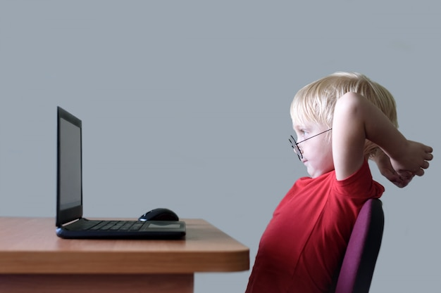 Funny blond boy in glasses resting at a laptop. internet and preschooler