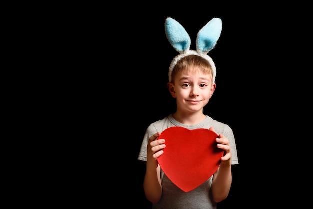 Забавный белокурый мальчик в заячьих ушах держит красную коробку в форме сердца на черной стене