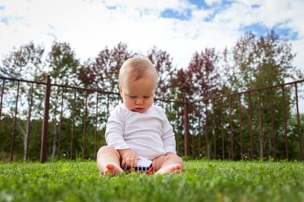 草の中に座って車のおもちゃで遊ぶ面白い金髪のかわいい赤ちゃん