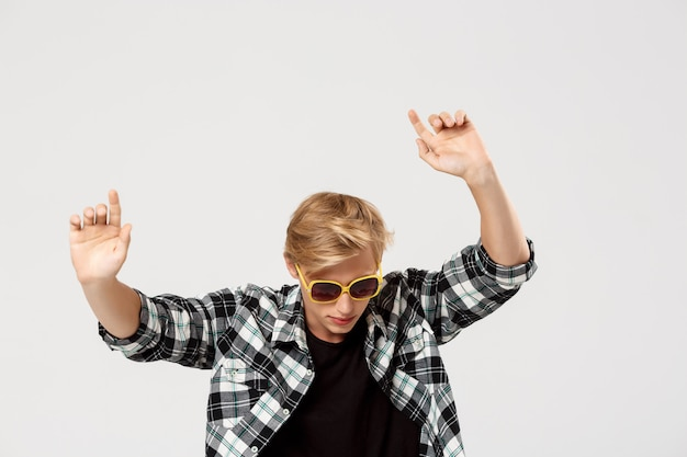 Funny blond handsome young man wearing sunglasses and casual plaid shirt dancing waving hands the air over grey wall