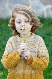 Funny blond kid with long hair smelling a flower