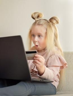 집에서 온라인으로 구매하는 신용 카드를 들고 재미있는 금발 백인 어린 소녀