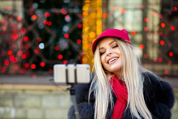 赤い帽子と毛皮のコートを着てスマートフォンで自画像を作る面白いブロンドの女の子。コピースペース