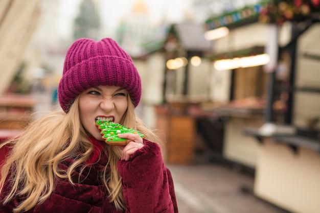 キエフの通りでおいしいクリスマスジンジャーブレッドクッキーを食べる面白いブロンドの女性