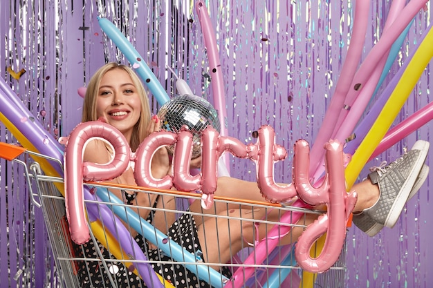 Funny blonde woman poses in shopping cart with colorful modeling balloons and disco ball
