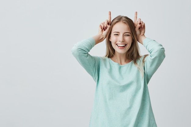 Funny blonde woman smiling broadly holding fingers above head. horns gesture