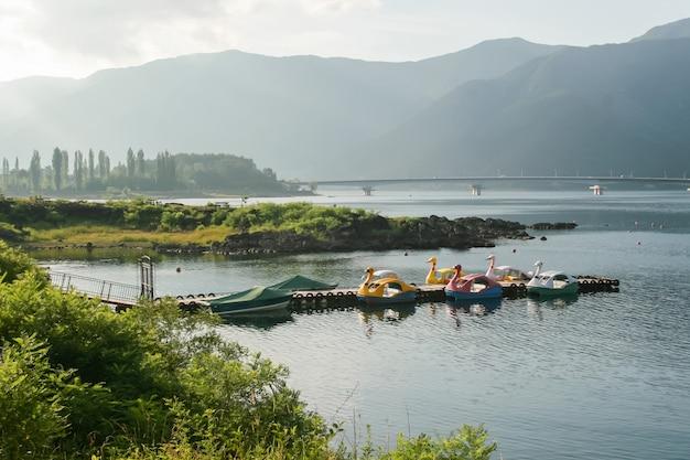 Смешные лодки, привязанные к деревянной пристани