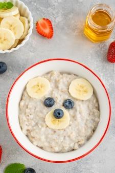 灰色のコンクリートの背景に果物とベリーで作られたクマの顔とオーツ麦のお粥と面白いボウル。子供のための食べ物のアイデア、上面図、コピースペース。