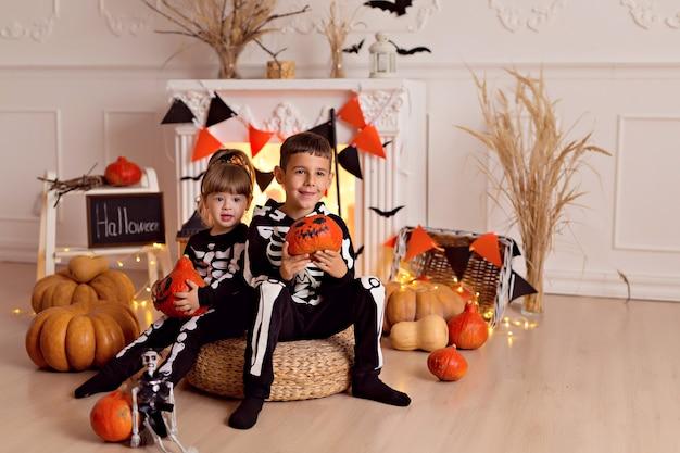 Забавный мальчик и девочка в костюме скелета на хэллоуин с тыквенным гнездом и метлой в помещении