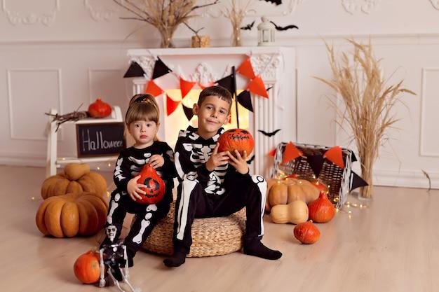 Забавный мальчик и девочка в костюмах скелета на хэллоуин