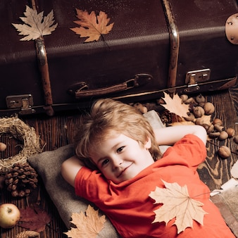 Funny boy are getting ready for autumn sale. adorable funny children toddlers. little child boy lies on wooden background and dreams of warm autumn.