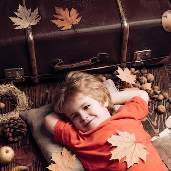 재미있는 소년이 가을 판매를 준비하고 있습니다. 사랑스러운 재미있는 어린이 유아. 어린 소년은 나무 배경에 누워 따뜻한 가을을 꿈꿉니다.