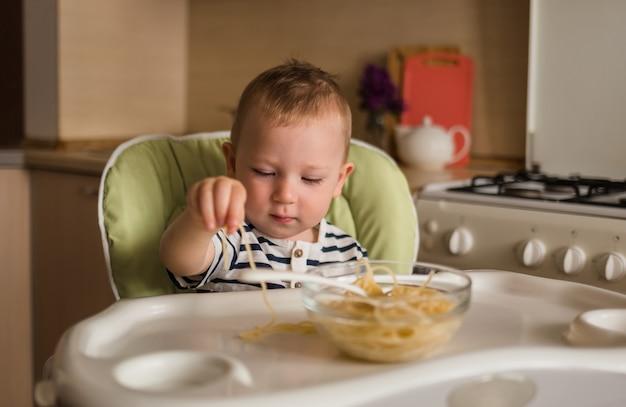 Забавный мальчик ест спагетти своими руками. маленький мальчик сидит на высоком стуле на кухне.