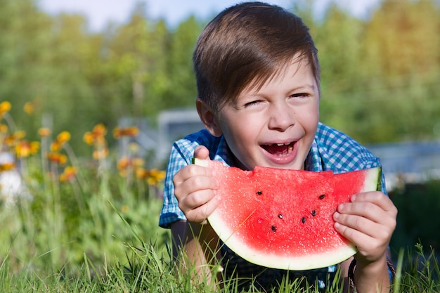 Funny boy eats watermelon outdoors in summer park