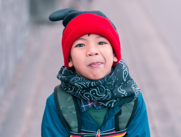Funny boy in full winter clothing walking on the street
