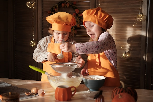 Funny boy and girl in orange chef costumes prepare pumpkin pie. kids are getting ready for thanksgiving. the concept of a family holiday
