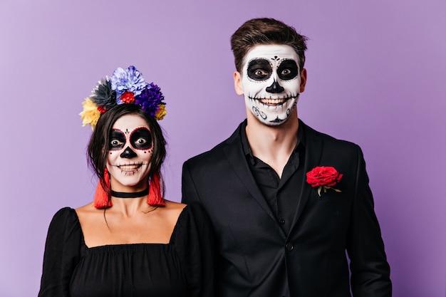 Un ragazzo e una ragazza divertenti con facce dipinte in stile messicano stanno guardando la telecamera con sorpresa e sorridendo.