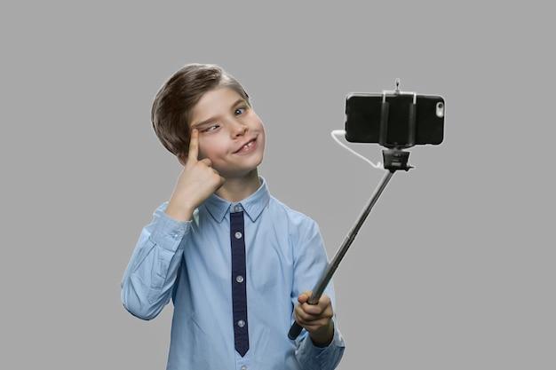 Забавный мальчик гримасничает при использовании монопод. ребенок дурачится, делая фото с помощью палки для селфи. дети, современные технологии, образ жизни.