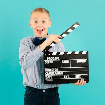 Funny boy holding clapperboard front view