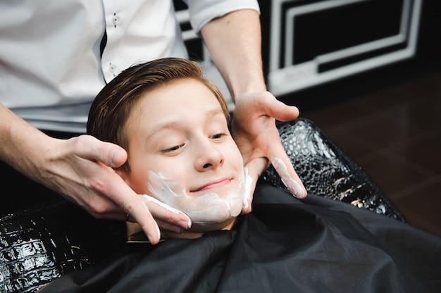 理髪店の黒いサロンケープで変な少年。理容師は彼の顔にシェービングブラシの助けを借りてシェービングフォームを適用します