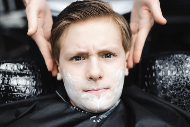 Забавный мальчик в черном салоне мыса в парикмахерской