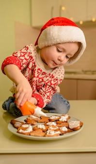 サンタヘルパーの帽子の面白い男の子がクッキーを作っています。家でクリスマスクッキーを調理する子供。
