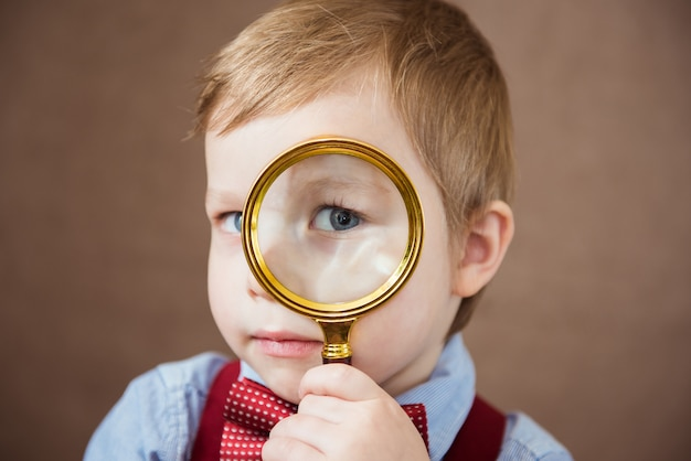Funny boy looking through magnifying glass with surprise. close up