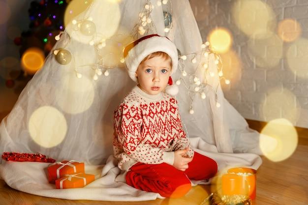 Забавный мальчик играет с подарками на полу в помещении на рождество