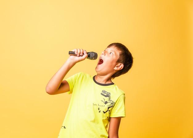Забавный мальчик поет с микрофоном на желтом фоне