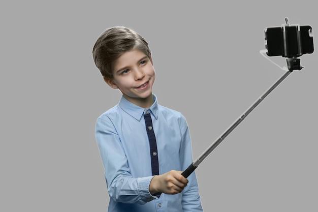 Забавный мальчик, использующий монопод на сером фоне. красивый ребенок фотографируя с палкой селфи. дети, современные технологии и развлечения.