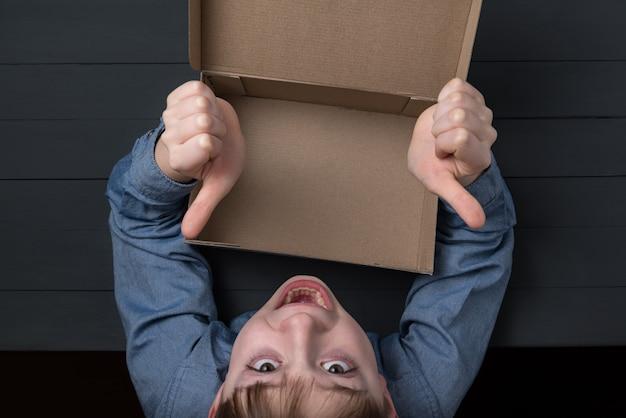 空の箱を開いて面白い少年は親指を現します。上面図