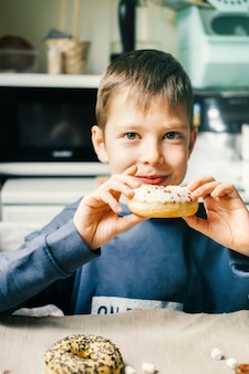 Funny boy with donut. child is having fun with doughnut. tasty food for kids. happy time at home with sweet food.