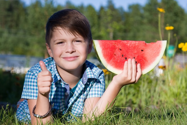 Funny boy with watermelon shows thumb up in summer park