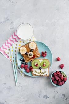 面白い朝食の動物はスプレッドでトーストに直面しています